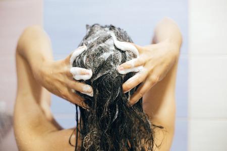 Jonge gelukkige vrouw die haar haar wast met shampoo, handen met schuimclose-up. Achterkant van mooie brunette meisje douche nemen en genieten van ontspannen tijd. Lichaams- en haarhygiëne, lifestyle concept Stockfoto
