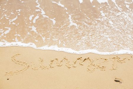 Summer sign on beach. Written summer text word on sandy beach  and sea waves with foam. Hello summer concept. Top view. Vacation, relax and travel. Copy space