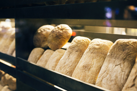 Fresh bread on shelves stand of a shop or bakery. Freshly baked bread loaves at window of store front. Organic pastry. Space for text