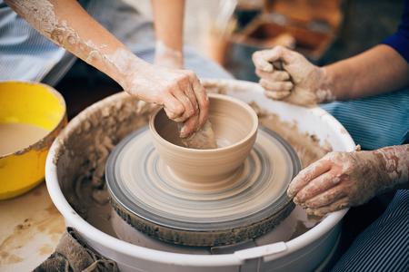 Hände von Erwachsenen und Kindern, die Keramik herstellen und mit nasser Tonnahaufnahme arbeiten. Prozess der Herstellung einer Schüssel aus Ton auf einem Rad mit schmutzigen Händen. Handgemachtes Festival im Sommerpark. Töpferwerkstatt. Standard-Bild