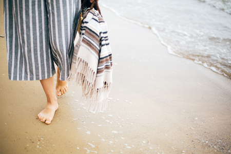 Stylish hipster girl walking barefoot on beach, holding bag  in hand, closeup. Summer vacation. Space for text. Calm moment. Boho woman relaxing at sea, enjoying walk on tropical island