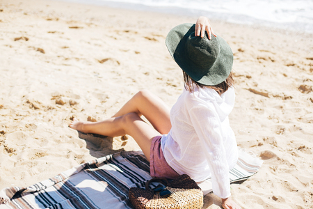 Stylish hipster girl in hat sitting on beach with straw bag and tanning. Summer vacation. Happy young boho woman relaxing and enjoying sunny warm day at ocean. Space for text