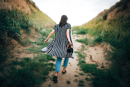 Stylish hipster girl running on sandy cliff  to sea and holding photo camera.  Happy young boho woman exploring tropical island at sandy cliff beach. Summer vacation. Space for text. 스톡 콘텐츠
