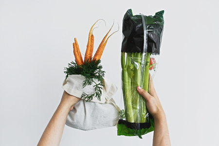 Hands holding reusable eco friendly bag with fresh carrots against celery in cellophane plastic package on white background. Zero waste grocery shopping. Ban plastic. Choose plastic free. Stock Photo