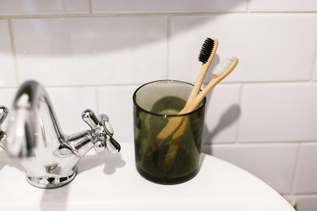 Zero waste bathroom concept. Eco natural bamboo toothbrushes in glass jar on sink in bathroom.  Plastic free items. Sustainable lifestyle. Oral hygiene 스톡 콘텐츠