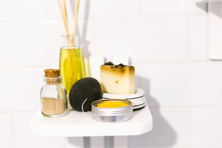 Zero waste bathroom concept. Eco natural shampoo, konjac sponge, fragrance oil, soap and ayurveda ubtan powder in glass on wooden shelf in bathroom, plastic free items. Sustainable lifestyle