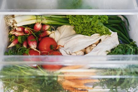 Zero waste grocery in fridge. Fresh vegetables in opened drawer in refrigerator. Plastic free carrots,tomatoes, mushrooms,radish,salad, arugula, zero waste shopping concept.Vegetarian diet