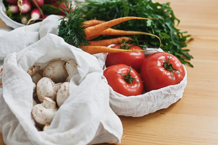 Fresh vegetables in eco cotton bags on wooden table in kitchen. Carrots,tomatoes, arugula, mushrooms from market in canvas reusable bags. Zero waste grocery shopping concept. ban plastic 스톡 콘텐츠