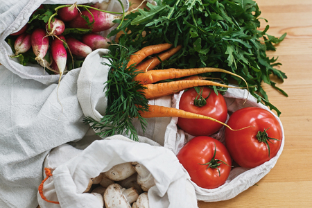 Zero waste grocery shopping concept. Reusable eco cotton bags with fresh vegetables carrots,tomatoes, arugula, mushrooms from market on wooden table. ban plastic. Sustainable lifestyle. 스톡 콘텐츠