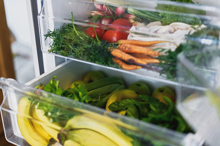 Zero waste grocery in fridge. Fresh vegetables in opened drawer in refrigerator. Plastic free carrots,tomatoes, mushrooms,bananas,salad, celery, apples, zero waste shopping. Grocery delivery