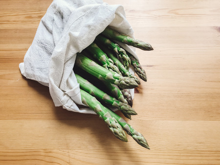 Reusable eco friendly bag with fresh asparagus on wooden table. Zero waste grocery shopping concept. Ban plastic. Choose plastic free. Organic cotton bags for shopping