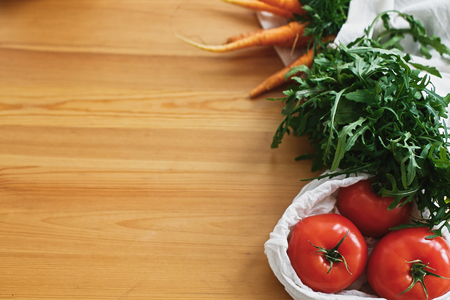 Fresh vegetables in eco cotton bags on wooden table in kitchen. Carrots,tomatoes, arugula from market in canvas reusable bags. Zero waste grocery shopping concept. ban plastic