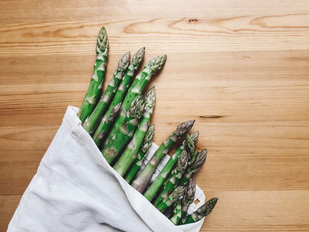 Reusable eco friendly bag with fresh asparagus on wooden table, flat lay. Zero waste grocery shopping concept. Ban plastic. Choose plastic free. Organic cotton bags for shopping
