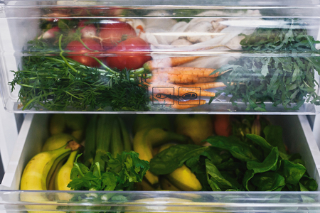Supermercado de desperdicio cero en la nevera. Verduras frescas en un cajón abierto en el frigorífico. Zanahorias, tomates, champiñones, plátanos, ensaladas, apio, manzanas sin plástico, compras sin desperdicio. Entrega de comestibles