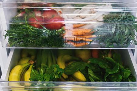 Zero sprechi di generi alimentari in frigo. Verdure fresche nel cassetto aperto in frigorifero. Carote senza plastica, pomodori, funghi, banane, insalata, sedano, mele, spesa zero rifiuti. Consegna della spesa