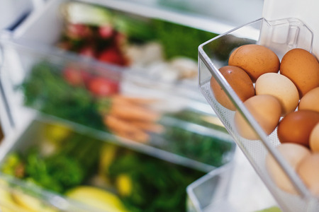 Eggs close up and plastic free carrots,tomatoes, mushrooms,bananas,salad, spinach, celery, apples in fridge. Zero waste grocery shopping. Fresh vegetables in opened drawer in refrigerator. 스톡 콘텐츠