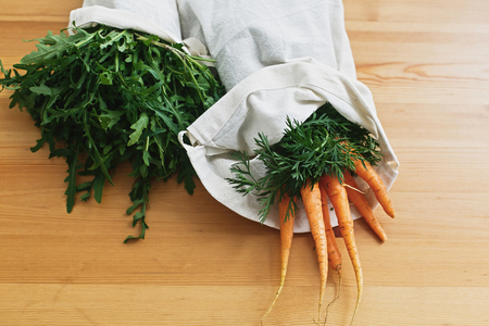 Reusable eco friendly bags with fresh vegetables carrots, arugula, on wooden table. ban plastic. Zero waste grocery shopping concept. Sustainable lifestyle.reuse, reduce, recycle