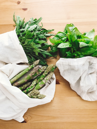 Zero waste grocery shopping concept. Reusable eco friendly bags with fresh asparagus, arugula,spinach,basil on wooden table, top view. Ban plastic. Choose plastic free.