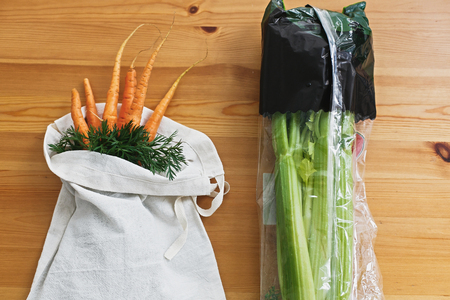 Reusable eco friendly bag with fresh carrots and celery in cellophane plastic package on wooden table, flat lay. Zero waste grocery shopping concept. Ban plastic. Choose plastic free