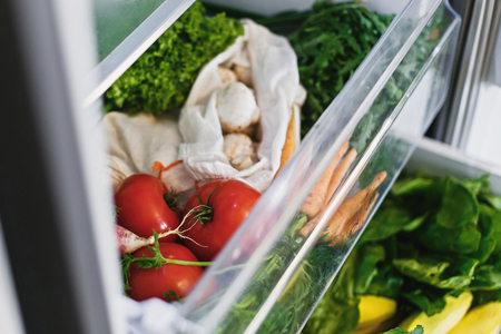 Fresh vegetables in opened drawer in refrigerator. Plastic free carrots,tomatoes, mushrooms,onions, radish,salad, arugula from market in fridge. Zero waste grocery shopping concept. 스톡 콘텐츠