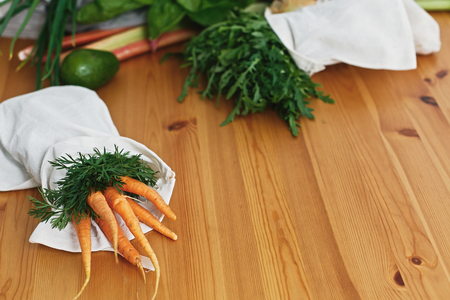 Zero waste grocery shopping concept. Reusable eco friendly bags with fresh vegetables carrots,arugula, mushrooms,avocado on wooden table. ban plastic. Sustainable lifestyle. 스톡 콘텐츠