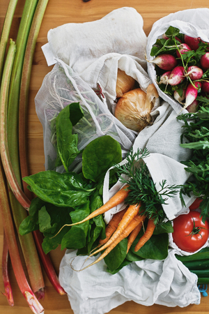 Zero waste grocery shopping concept,flat lay. Reusable eco friendly bags with fresh vegetables carrots,tomatoes, spinach,arugula, mushrooms,rhubarb,onions on wooden table. ban plastic. 스톡 콘텐츠