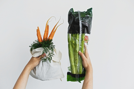 Choose plastic free. Hands holding reusable eco friendly bag with fresh carrots against celery in cellophane plastic package on white background. Zero waste grocery shopping. Ban plastic. Stock Photo