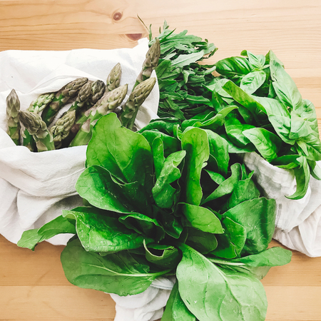 Reusable eco friendly bag with fresh asparagus, arugula,spinach on wooden table, top view. Zero waste grocery shopping concept. Ban plastic. Choose plastic free. Organic cotton bags 스톡 콘텐츠
