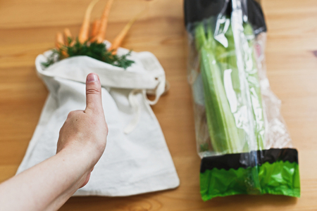 Reusable eco friendly bag with fresh carrots and celery in cellophane plastic package on wooden table, flat lay. Approving hand plastic free.  Zero waste grocery shopping concept.