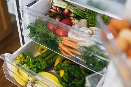 Fresh grocery delivery. Plastic free carrots,tomatoes, mushrooms,bananas,salad, spinach, celery, apples in fridge. Zero waste shopping. Fresh vegetables in opened drawer in refrigerator. Vegan