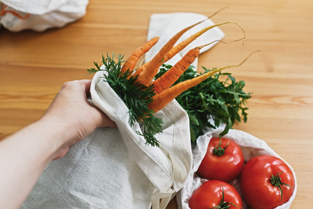 Zero waste grocery shopping. Hands holding reusable eco friendly canvas bag with fresh carrots and greenery on background of table with vegetables. Ban plastic. Choose plastic free.