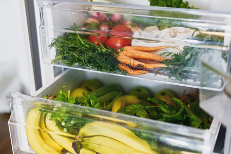 Plastic free carrots,tomatoes, mushrooms,bananas,salad, spinach, celery, apples in fridge. Zero waste grocery shopping. Fresh vegetables in opened drawer in refrigerator. Vegetarian diet