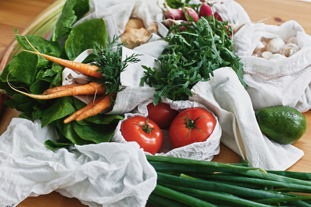 Zero waste grocery shopping concept. Reusable eco friendly bags with fresh vegetables carrots,tomatoes, arugula, mushrooms from market on wooden table. ban plastic. Sustainable lifestyle.