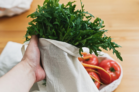 Hands holding reusable eco friendly canvas bag with fresh green arugula on background of table with vegetables. Zero waste grocery shopping. Ban plastic. Choose plastic free. 스톡 콘텐츠