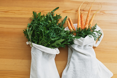 Zero waste grocery shopping concept. Reusable eco friendly bags with fresh vegetables carrots, arugula, on wooden table, flat lay. ban plastic. Sustainable lifestyle.reuse, reduce, recycle