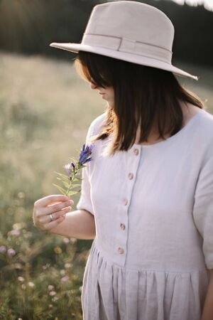 Stylish girl in rustic dress holding wildflower in hand, standing in sunny meadow in mountains.Boho woman gathering flowers in countryside at sunset, rural simple life. Atmospheric image Фото со стока