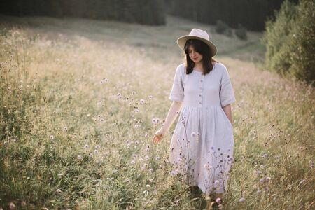Stylish girl in linen dress walking among wildflowers in sunny meadow in mountains. Boho woman relaxing in countryside flowers at sunset, simple life. Atmospheric image. Space text