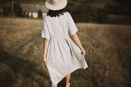 Stylish girl in linen dress and hat walking barefoot among herbs and wildflowers in sunny field in mountains. Boho woman relaxing in countryside, simple rustic life. Atmospheric image