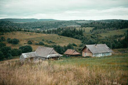 Schöne alte Holzhäuser auf Hügeln und sonniger Wiese in den Bergen. Ländliches einfaches Leben auf dem Lande. Atmosphärisches Bild. Berglandschaft