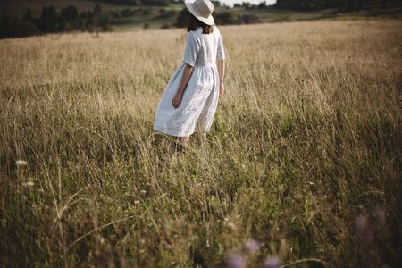 Stylish girl in linen dress dancing among herbs and wildflowers in sunny meadow in mountains. Boho woman relaxing in countryside, simple rustic life style. Atmospheric image. Space text Фото со стока