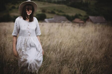 Stylish girl in linen dress and hat walking among herbs and wildflowers in field. Boho woman enjoying day in countryside, simple slow life style. Space for text. Atmospheric image Фото со стока