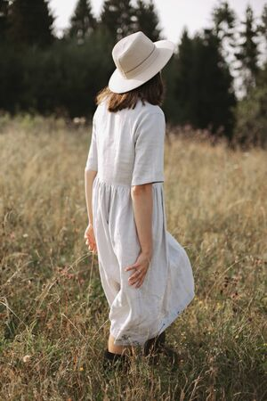 Stylish girl in linen dress and hat walking among herbs and wildflowers, looking at field. Boho woman relaxing in countryside, simple slow life style.  Atmospheric image