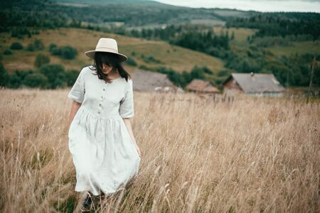 Stylish girl in linen dress and hat walking among herbs and wildflowers in field. Boho woman enjoying day in countryside, simple slow life style. Space for text. Atmospheric image