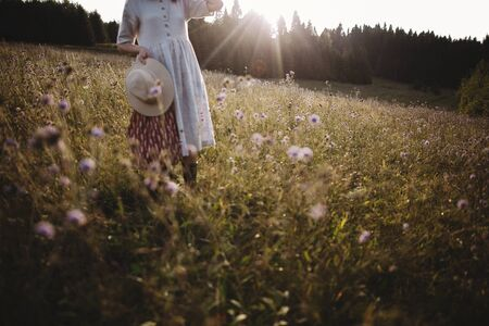 Wildflowers and herbs in sunny meadow in mountains and blurred image of stylish girl in rustic dress and hat. Boho woman relaxing in countryside at sunset, simple life. Atmospheric image Фото со стока