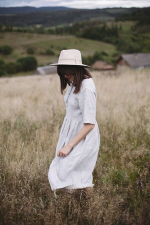 Stylish girl in linen dress and hat walking among herbs and wildflowers in field. Boho woman relaxing in countryside, simple slow life style. Space for text. Atmospheric image Фото со стока