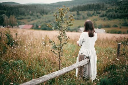 Stylish girl in linen dress standing at aged wooden fence among herbs and wildflowers in meadow. Boho woman relaxing in countryside, simple slow life style. Atmospheric image. Space text
