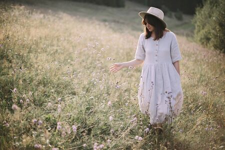 Stylish girl in rustic dress and hat walking among wildflowers and herbs in sunny meadow in mountains. Boho woman relaxing in countryside at sunset, simple life. Atmospheric image Фото со стока