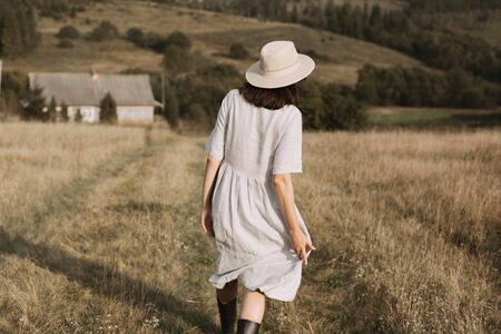 Stylish girl in linen dress and hat walking among herbs and wildflowers in sunny field in mountains. Boho woman relaxing in countryside, simple rustic life. Atmospheric image. Space text