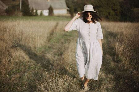 Stylish girl in linen dress and hat walking barefoot among herbs and wildflowers in sunny field in mountains. Boho woman smiling in countryside, simple rustic life. Atmospheric image Stock Photo