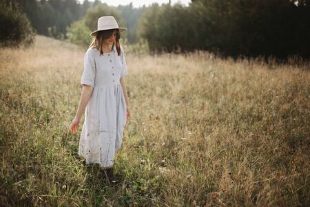 Stylish girl in linen dress walking among herbs and wildflowers in sunny meadow in mountains. Boho woman relaxing in countryside, simple rustic life style. Atmospheric image. Space text